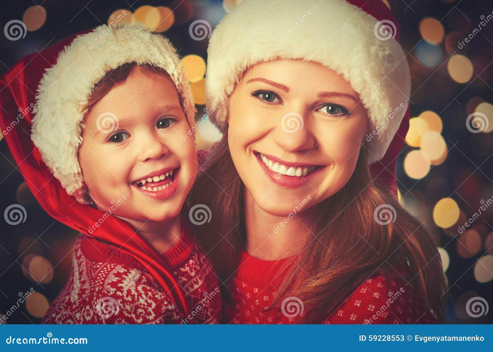 Madre feliz de la familia y pequeño niño que juegan en la Navidad
