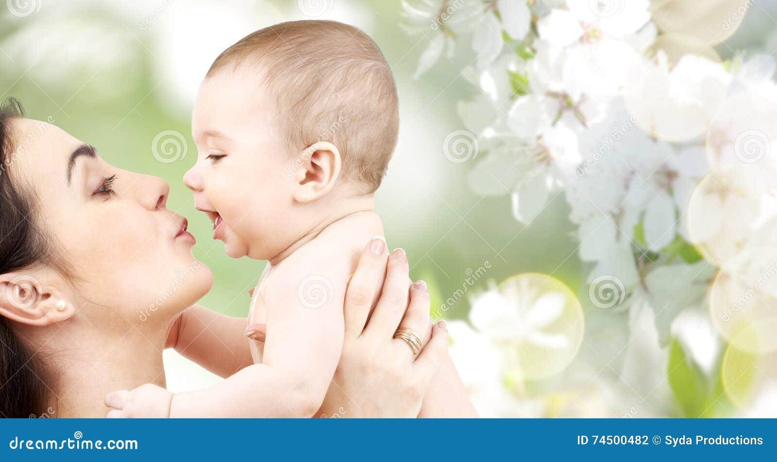 Madre feliz que besa al bebé adorable