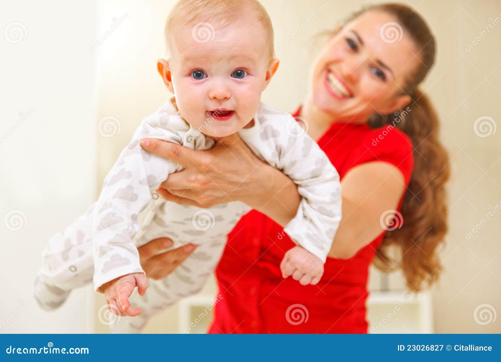 Madre feliz y bebé encantador que juegan en el diván