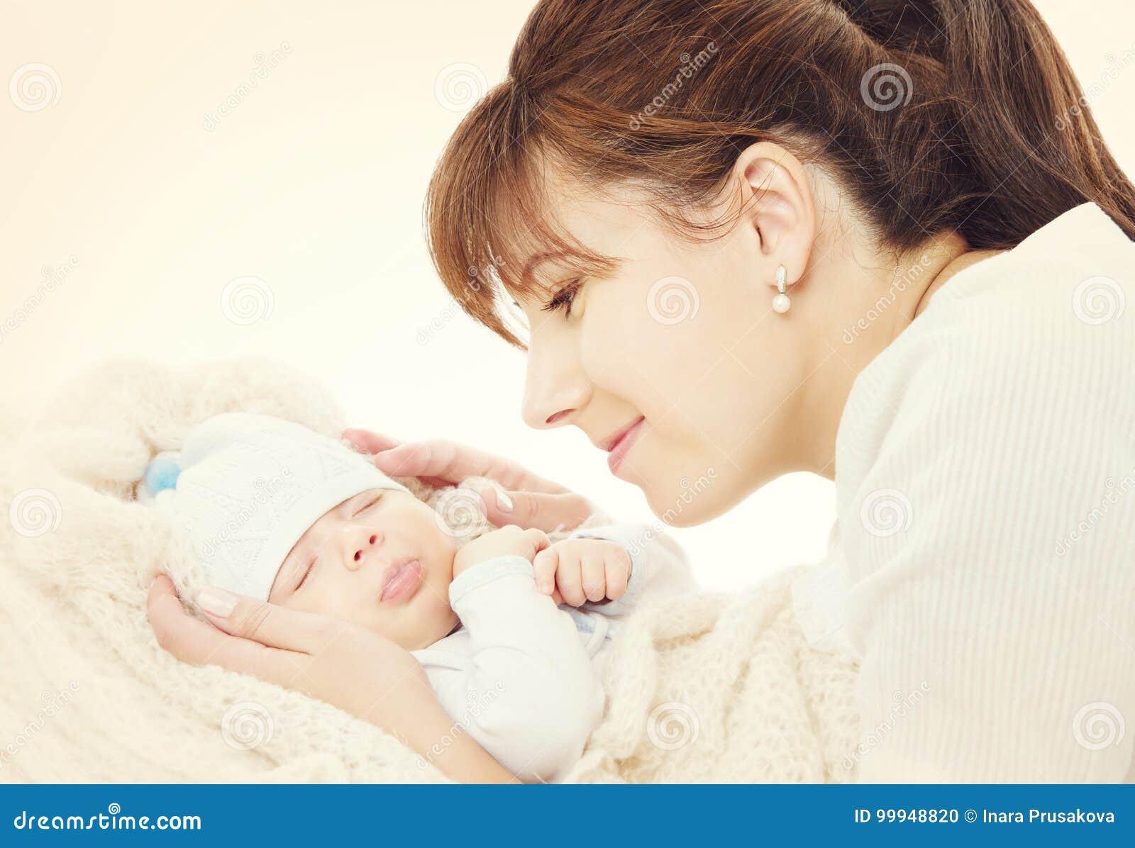 Madre feliz y bebé recién nacido durmiente, mamá que mira a recién nacido