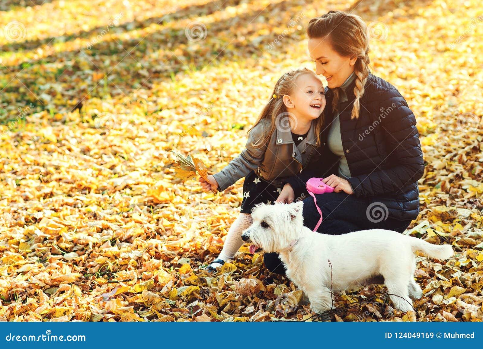Madre feliz y su hija que juegan con el perro en parque del otoño Familia, animal doméstico, animal doméstico y concepto de la fo