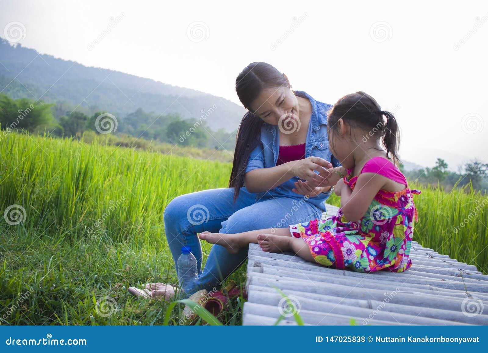 Madre feliz y su juego de ni?os al aire libre que se divierten, tierra trasera del campo verde del arroz