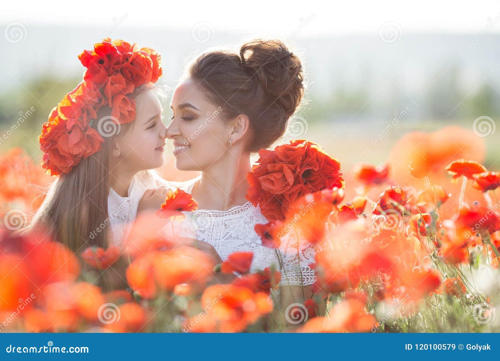 Madre hermosa y su hija que juegan en campo de flor de la primavera