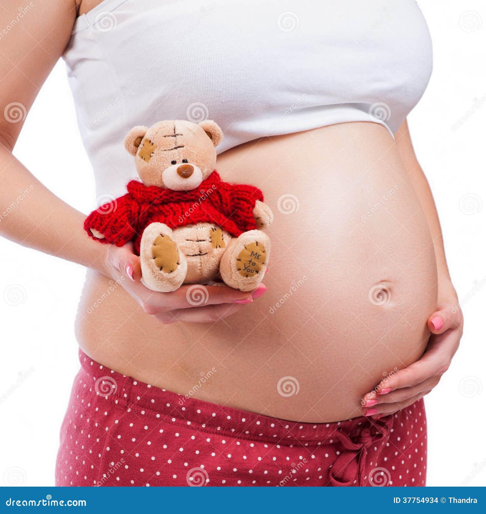 Madre incinta che mostra la sua pancia e che tiene un orsacchiotto