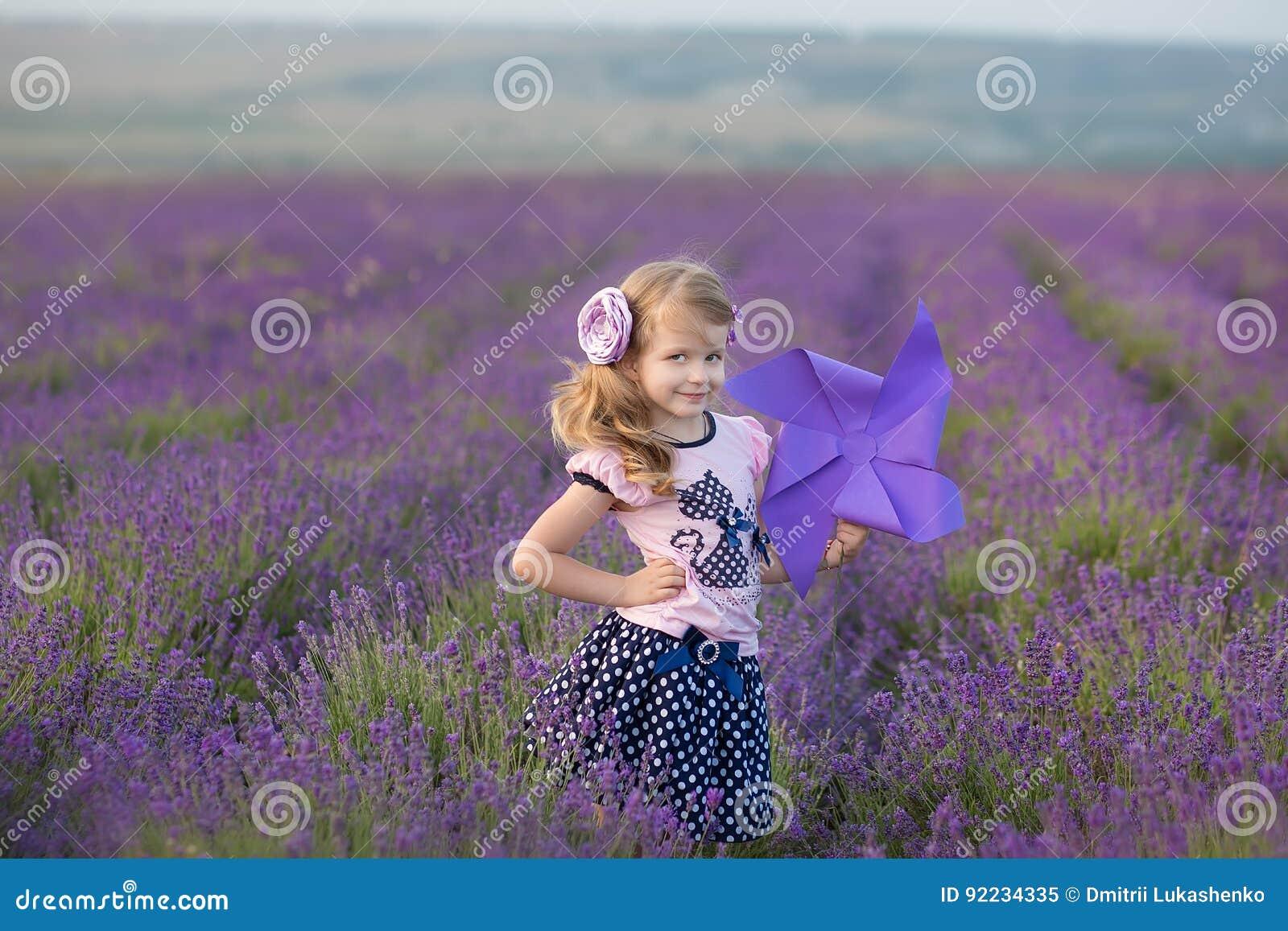Madre joven con la hija joven que sonríe en el campo de la lavanda Hija que se sienta en las manos de la madre Muchacha en colori