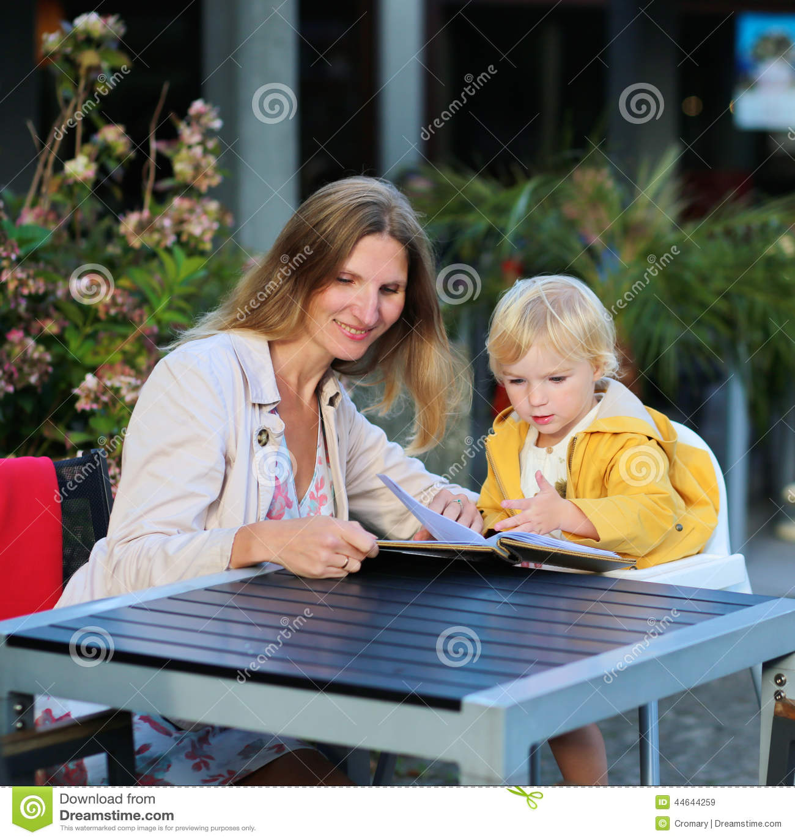 Madre joven con la pequeña hija que tiene comida en café del aire libre