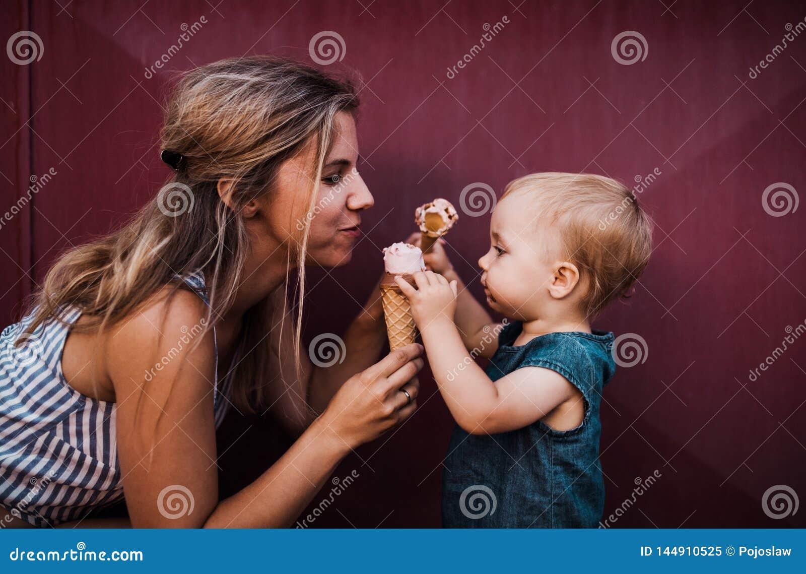 Madre joven con la peque?a ni?a peque?a al aire libre en el verano, comiendo el helado