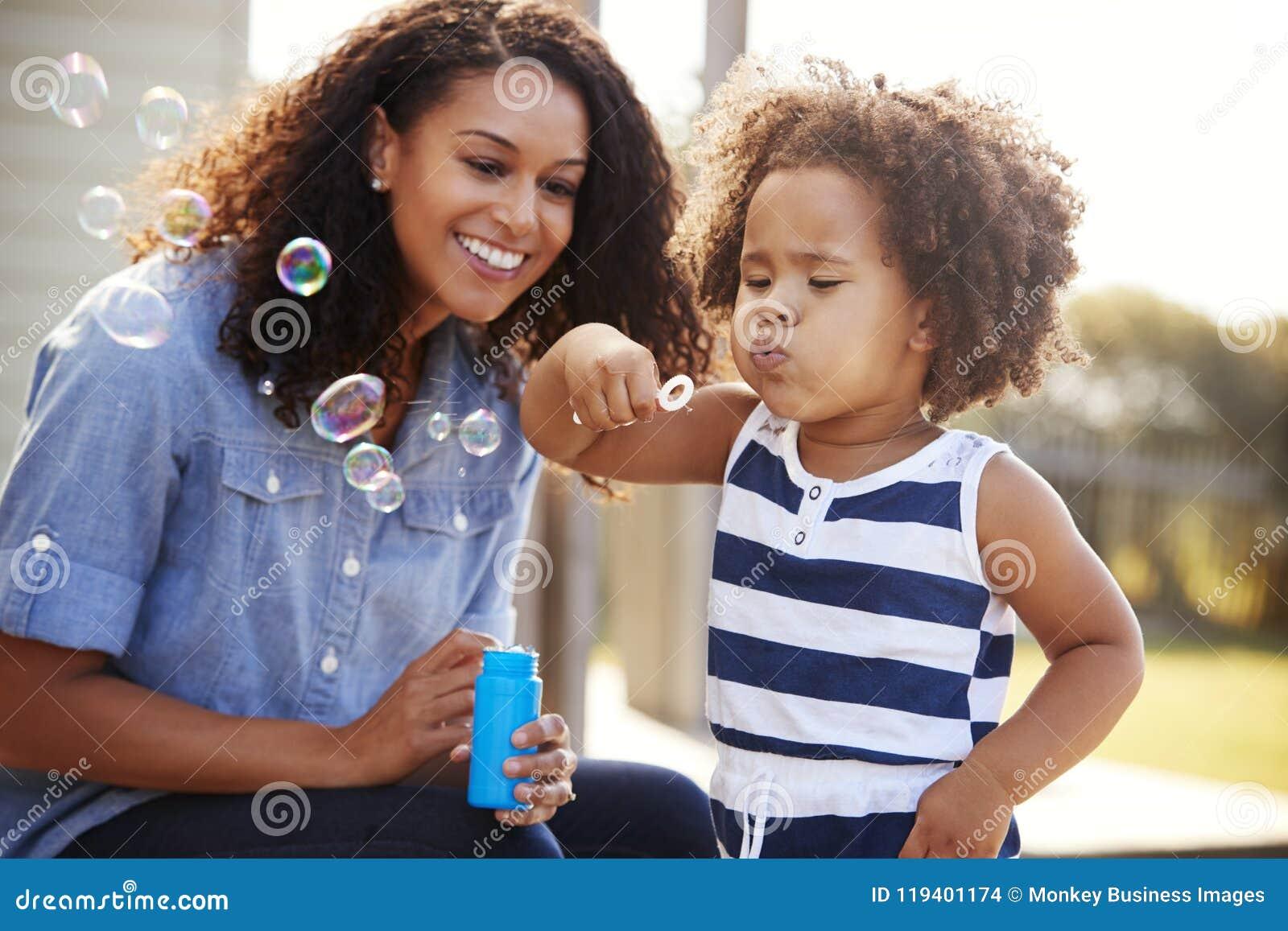 Madre joven de la raza mixta y burbujas que soplan de la hija afuera