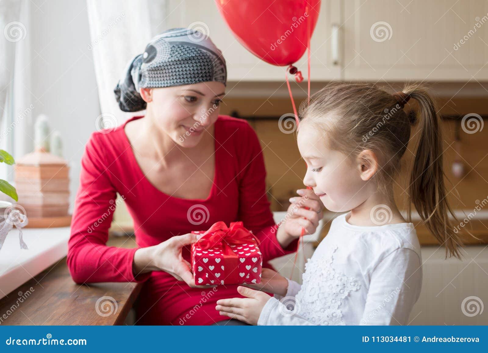 Madre joven, enfermo de cáncer, y su hija linda, celebrando cumpleaños con los globos y los presentes