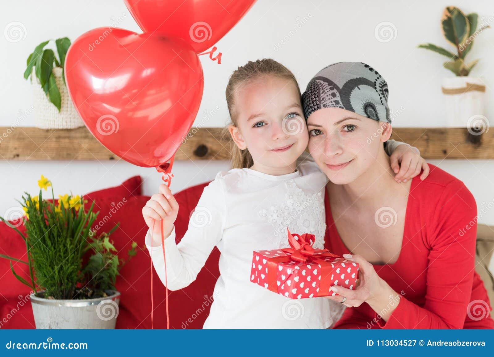 Madre joven, enfermo de cáncer, y su hija linda, celebrando el hogar de vuelta del hospital Fiesta agradable del hogar o de cumpl