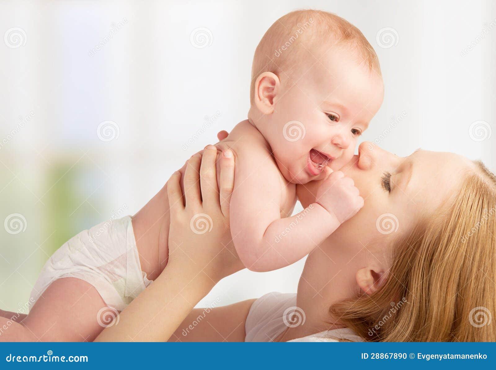 Madre joven feliz que besa a un bebé