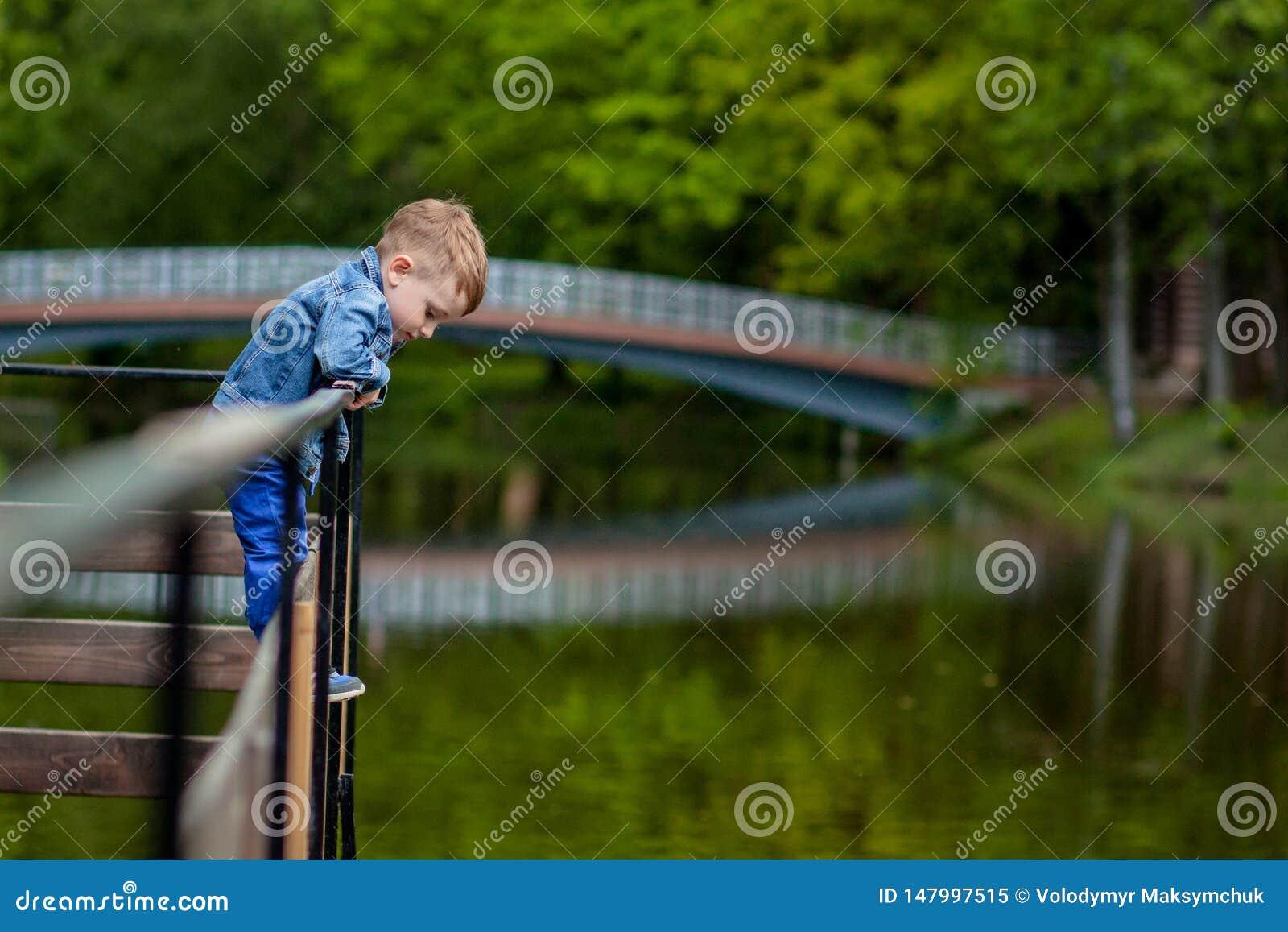 Madre joven feliz que juega y que se divierte con su peque?o hijo del beb? en d?a caliente de la primavera o de verano en el parq