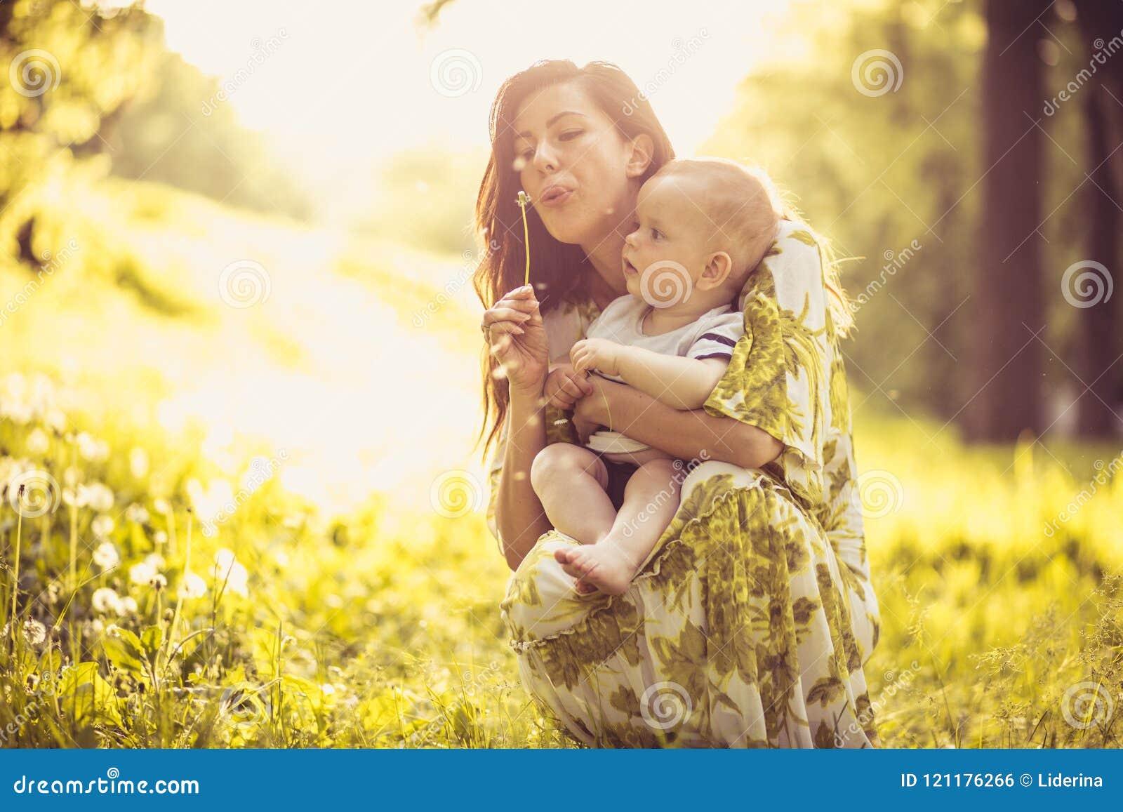 Madre joven hermosa con su hijo del bebé en la naturaleza Retrato