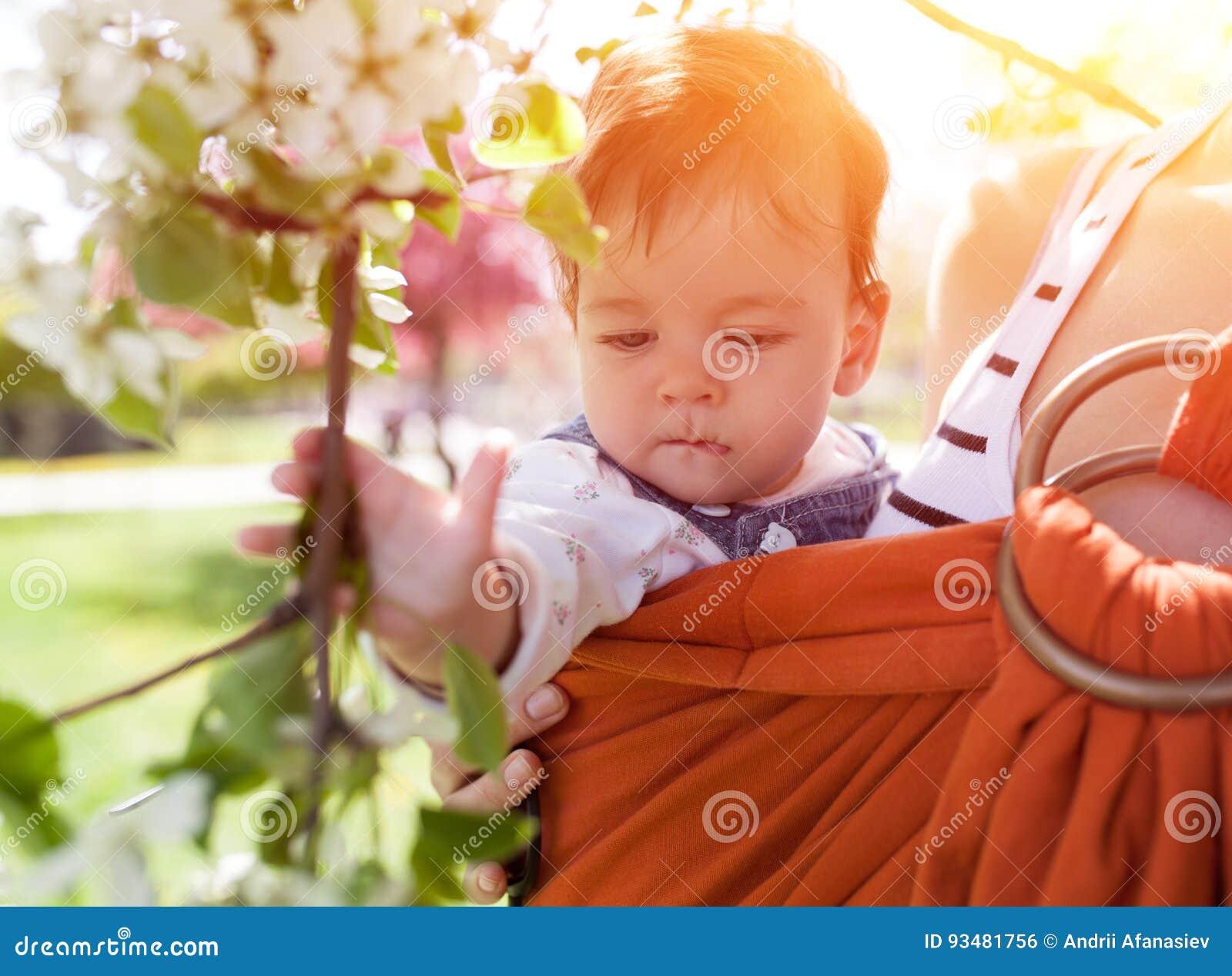 Madre joven irreconocible con su bebé infantil en honda