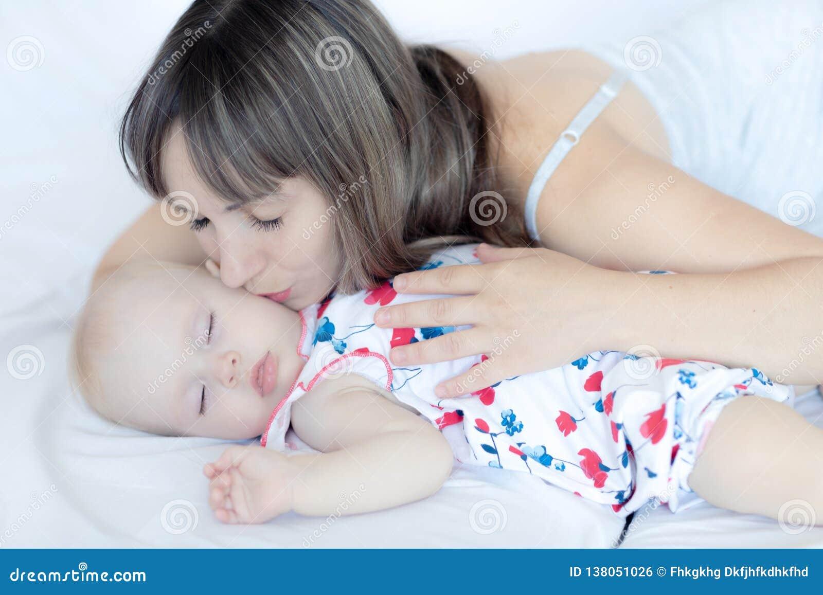 Madre joven que abraza a su niño recién nacido Bebé del oficio de enfermera de la mamá