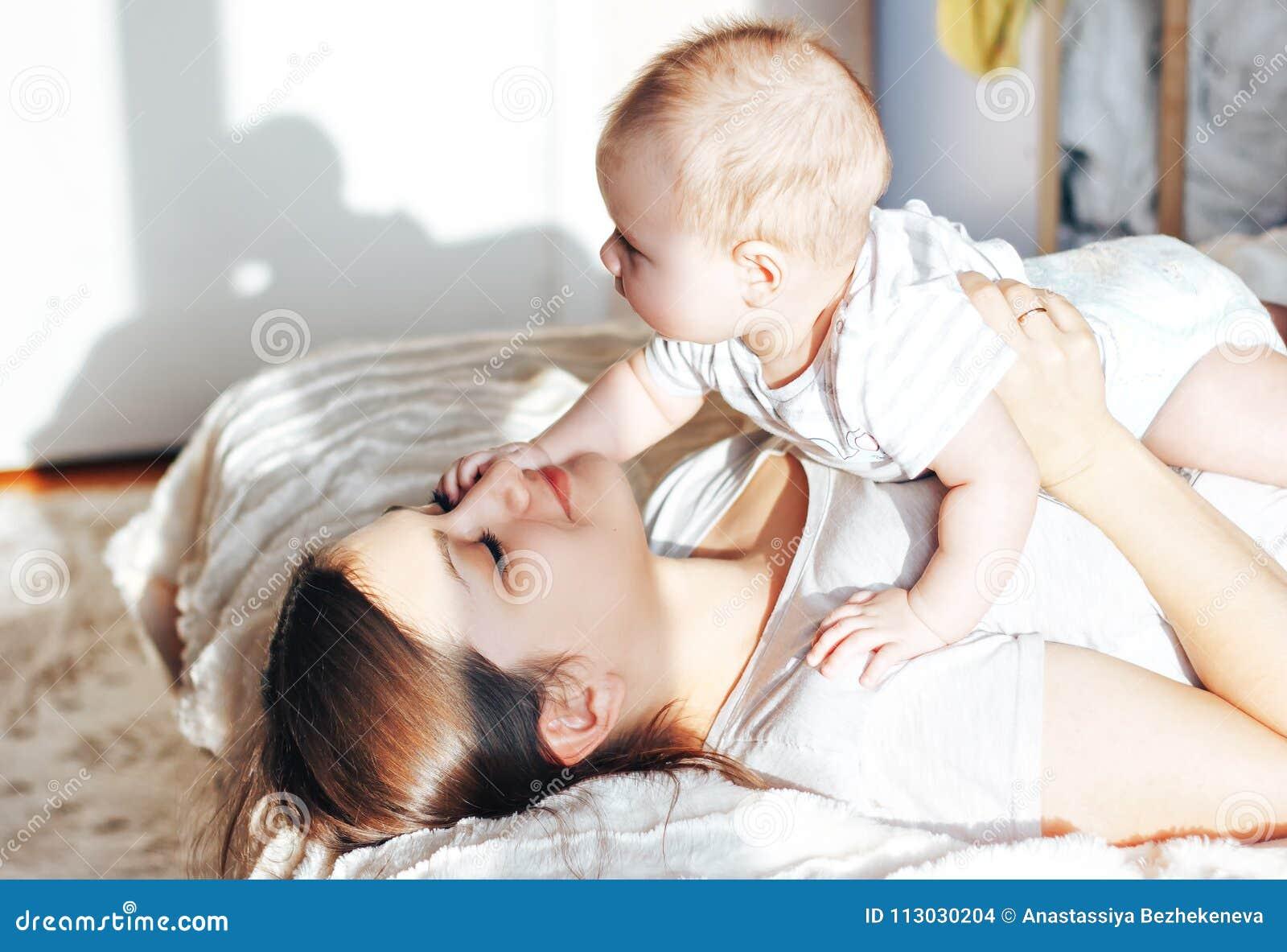 Madre joven que juega con su bebé en la cama, riendo