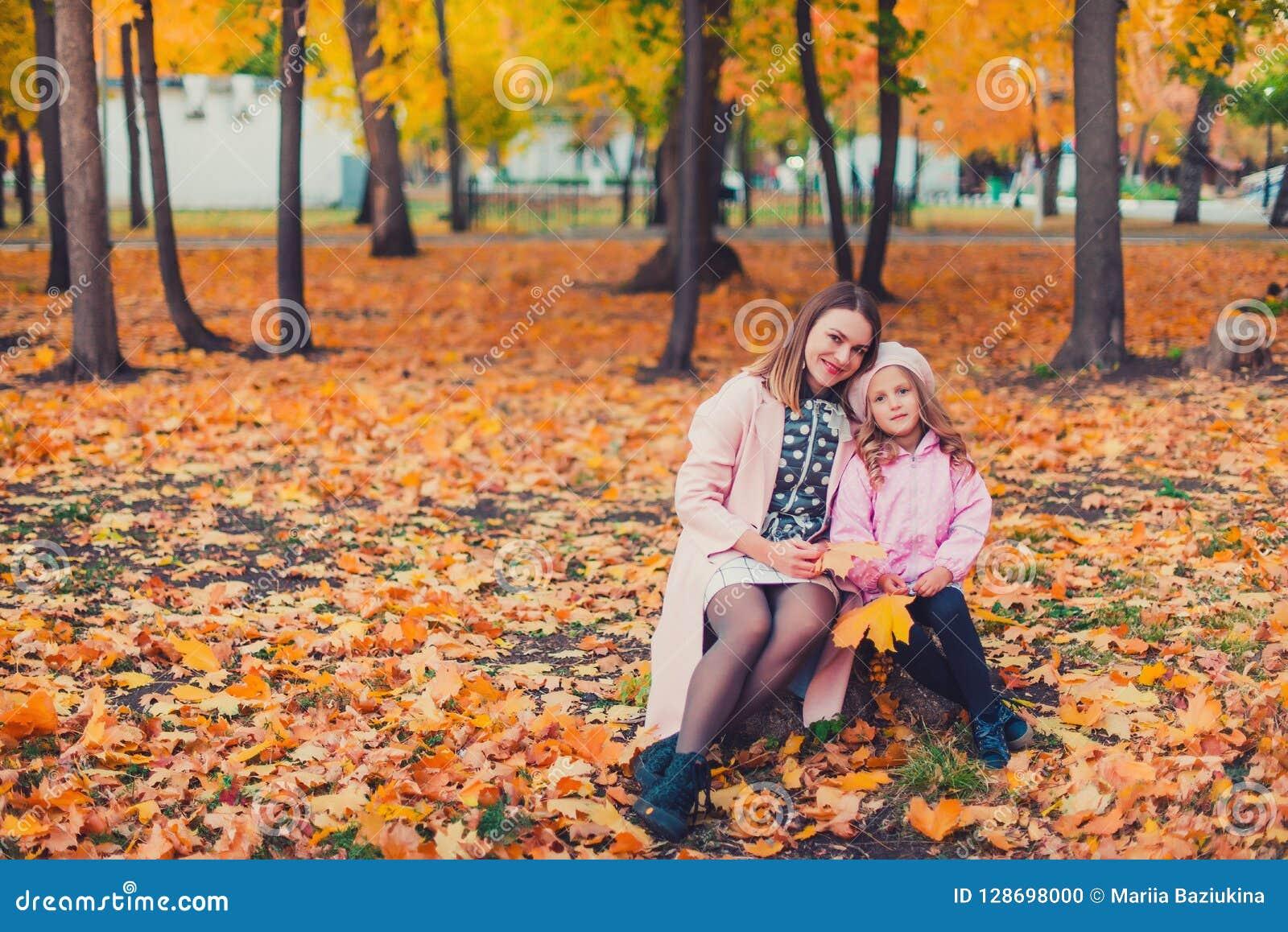 Madre joven que juega con su hija en parque del otoño