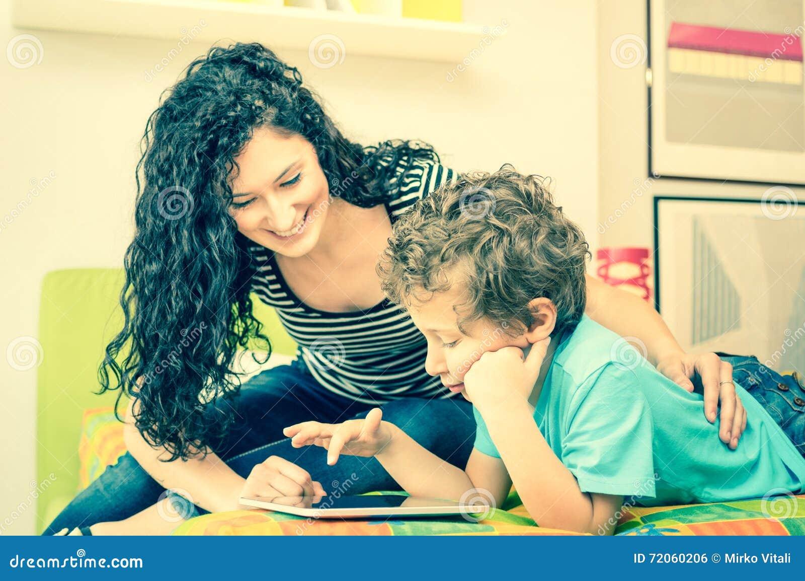 Madre joven que se divierte que aprende con el hijo que usa la tableta en cama