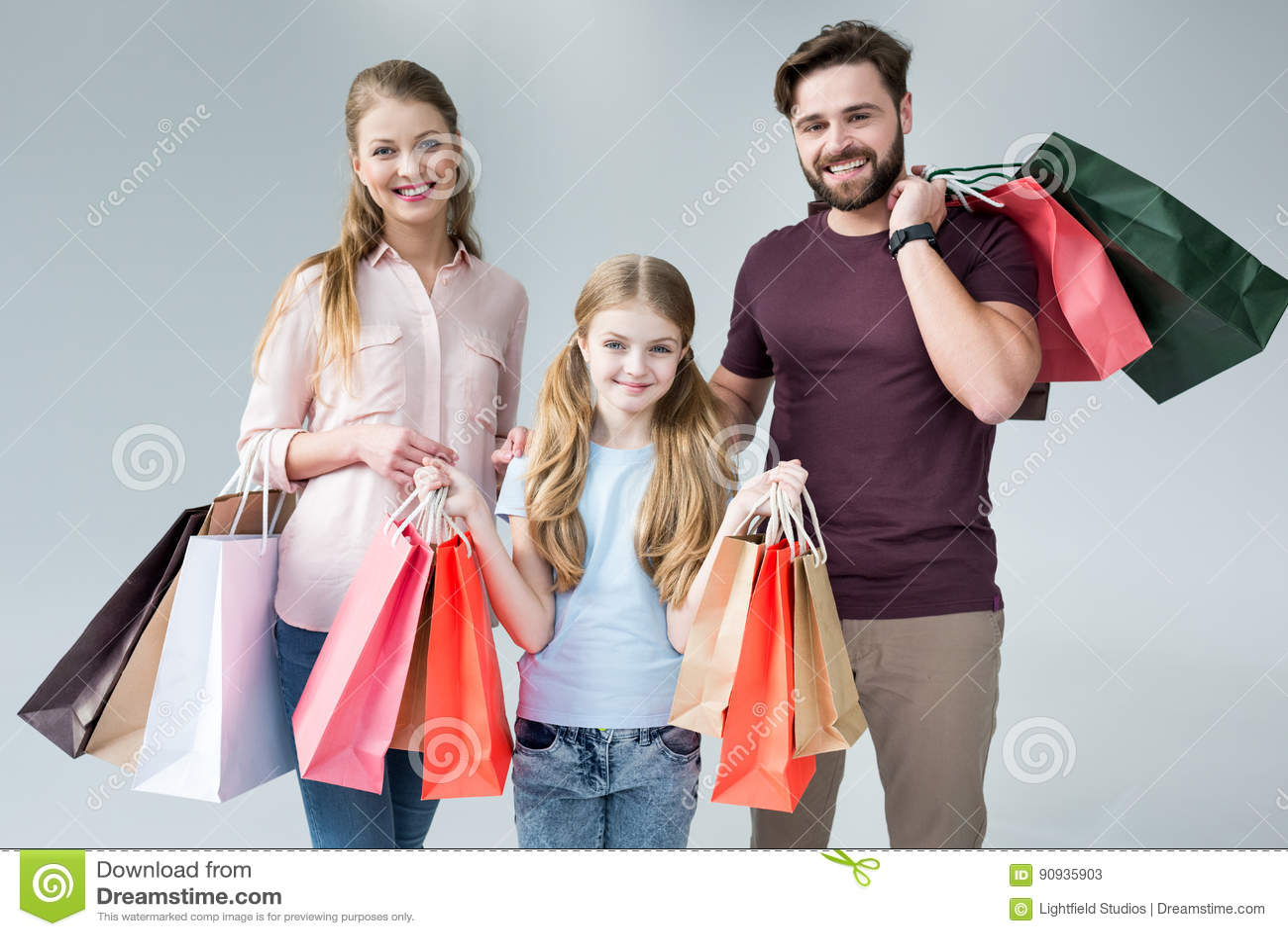 Madre, padre e figlia stanti con i sacchetti della spesa