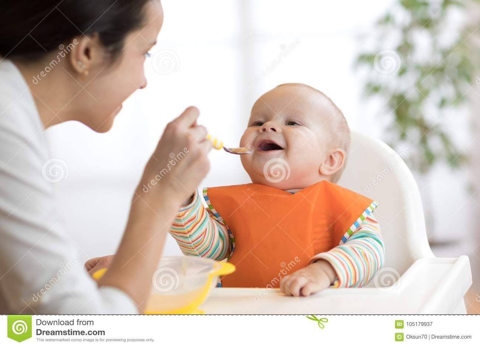Madre que alimenta a su bebé con la cuchara Mime a dar la comida sana a su niño adorable en casa