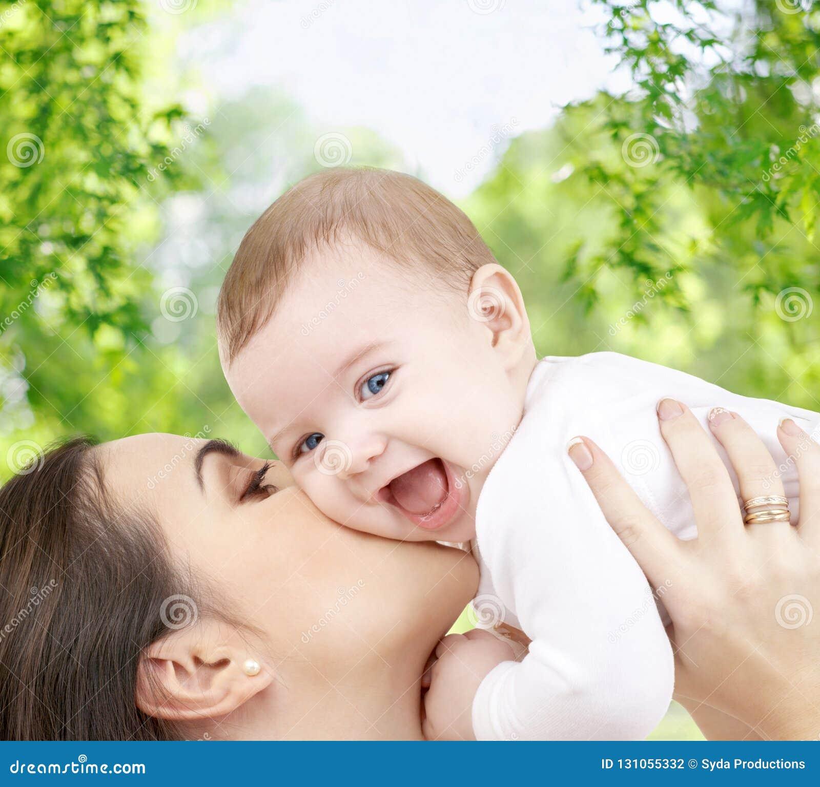Madre que besa al bebé sobre fondo natural verde