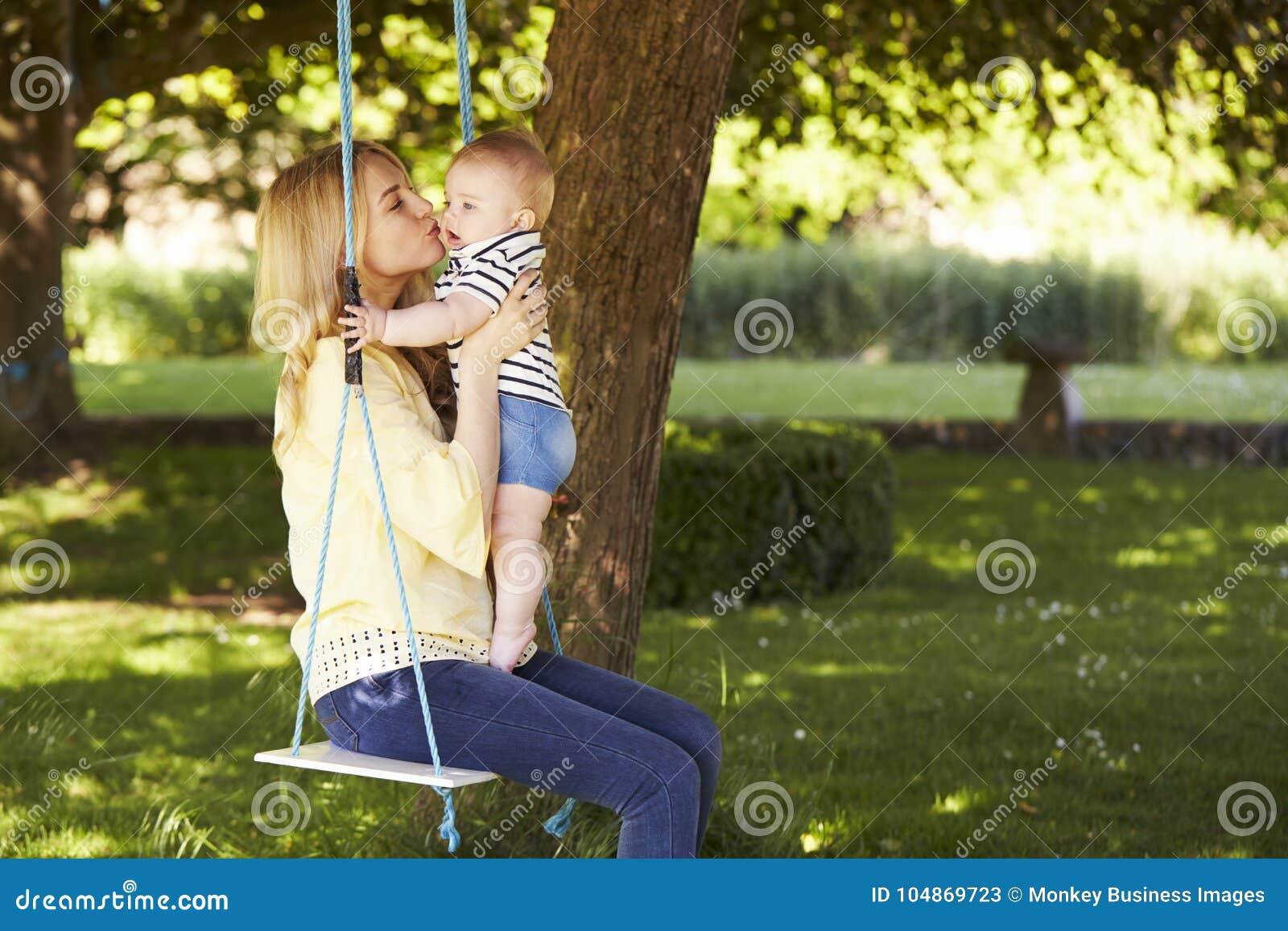 Madre que besa al hijo del bebé como ellos Sit On Garden Swing