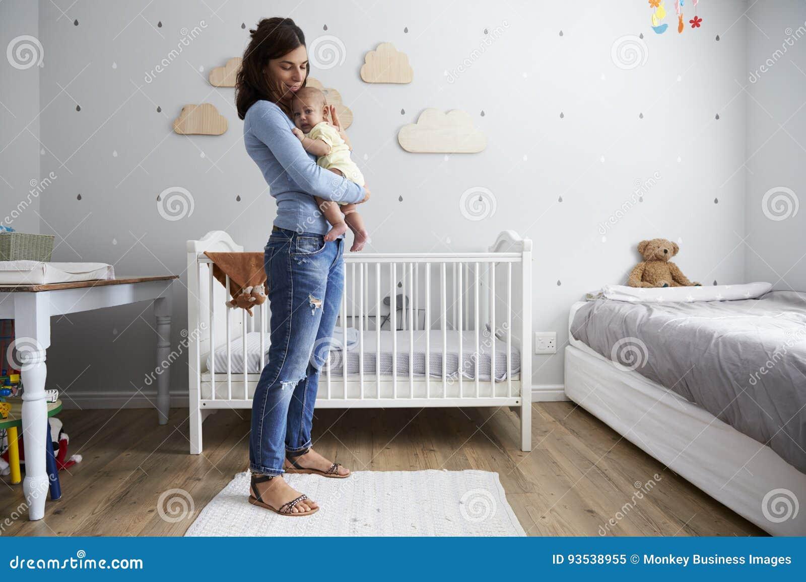 Madre que conforta al hijo recién nacido del bebé en cuarto de niños