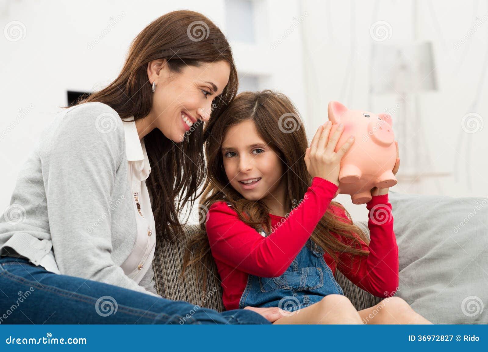 Madre que mira a la hija que sostiene Piggybank