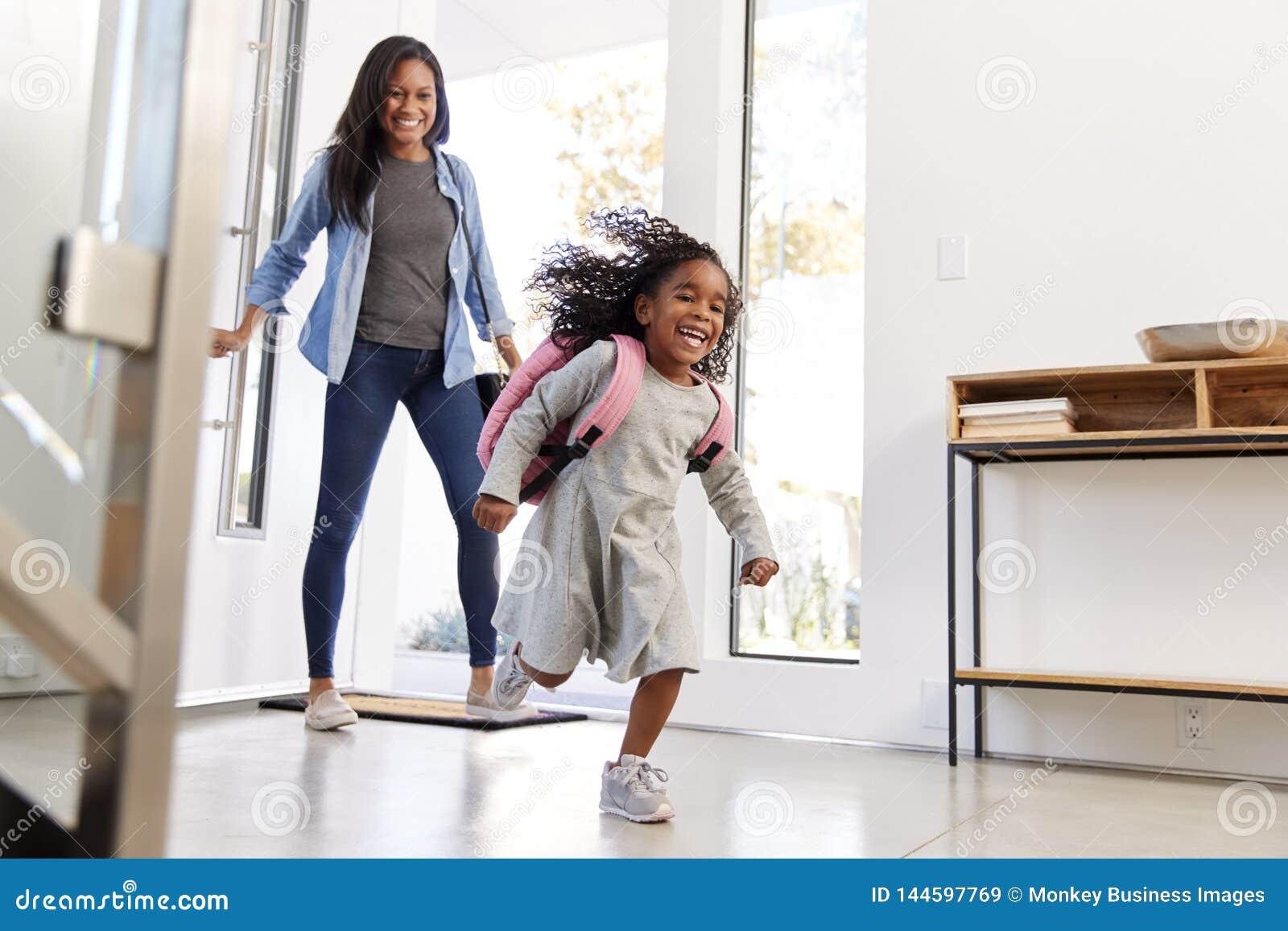 Madre que recoge y que trae el hogar de la hija después de escuela