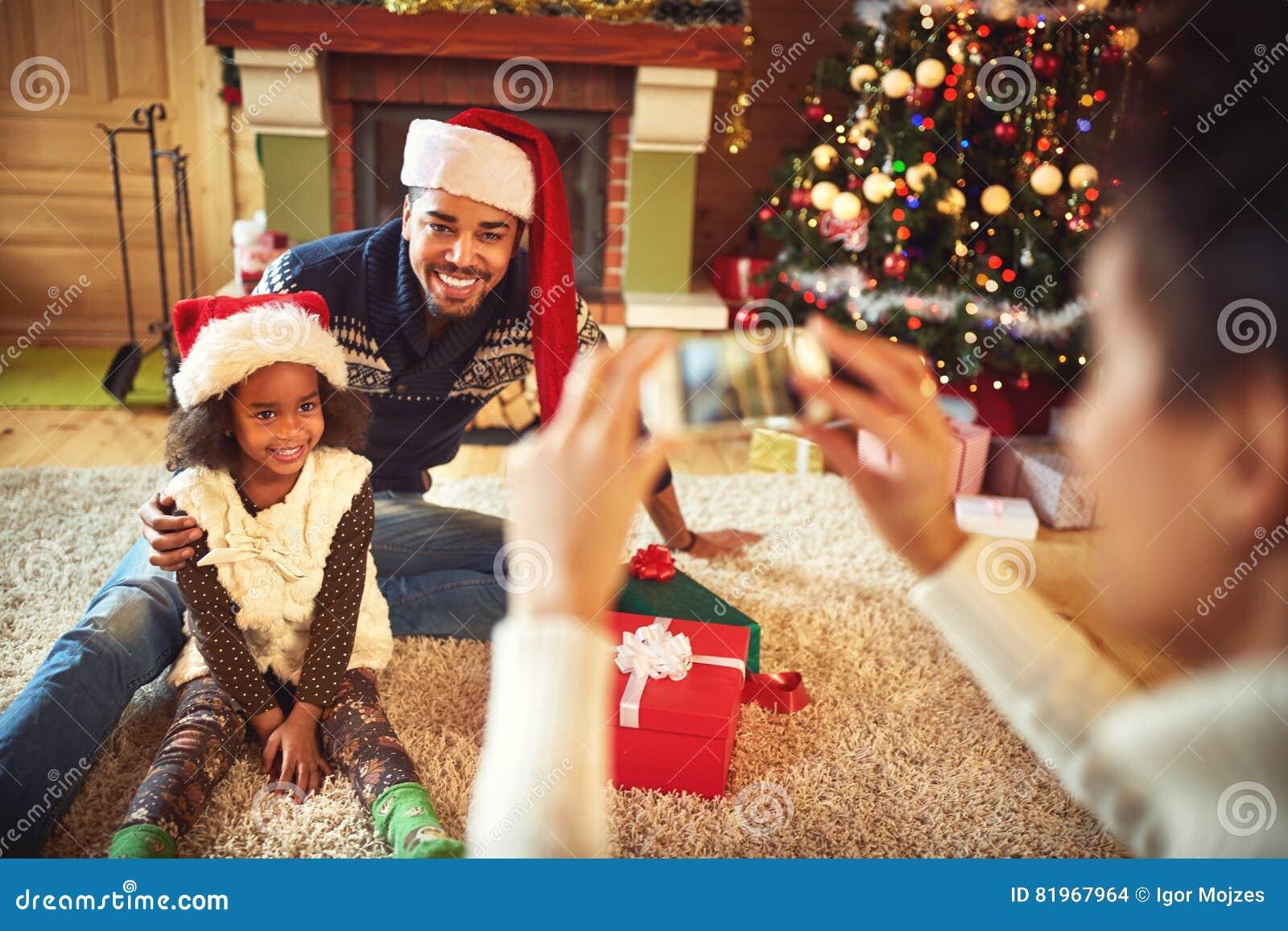 Madre que toma la imagen del padre y de la hija sonrientes en Papá Noel ha