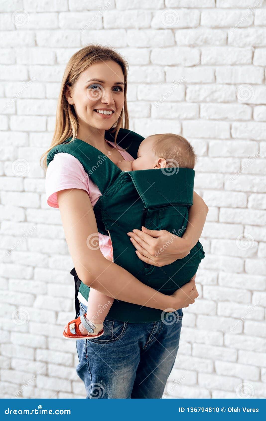 Madre sonriente con el bebé recién nacido en honda del bebé