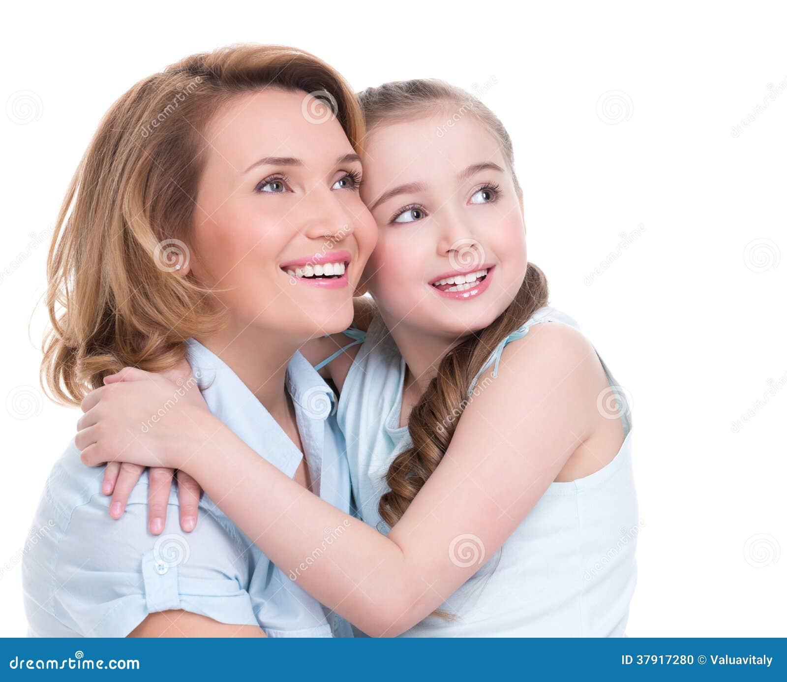 Madre sonriente e hija joven que miran para arriba