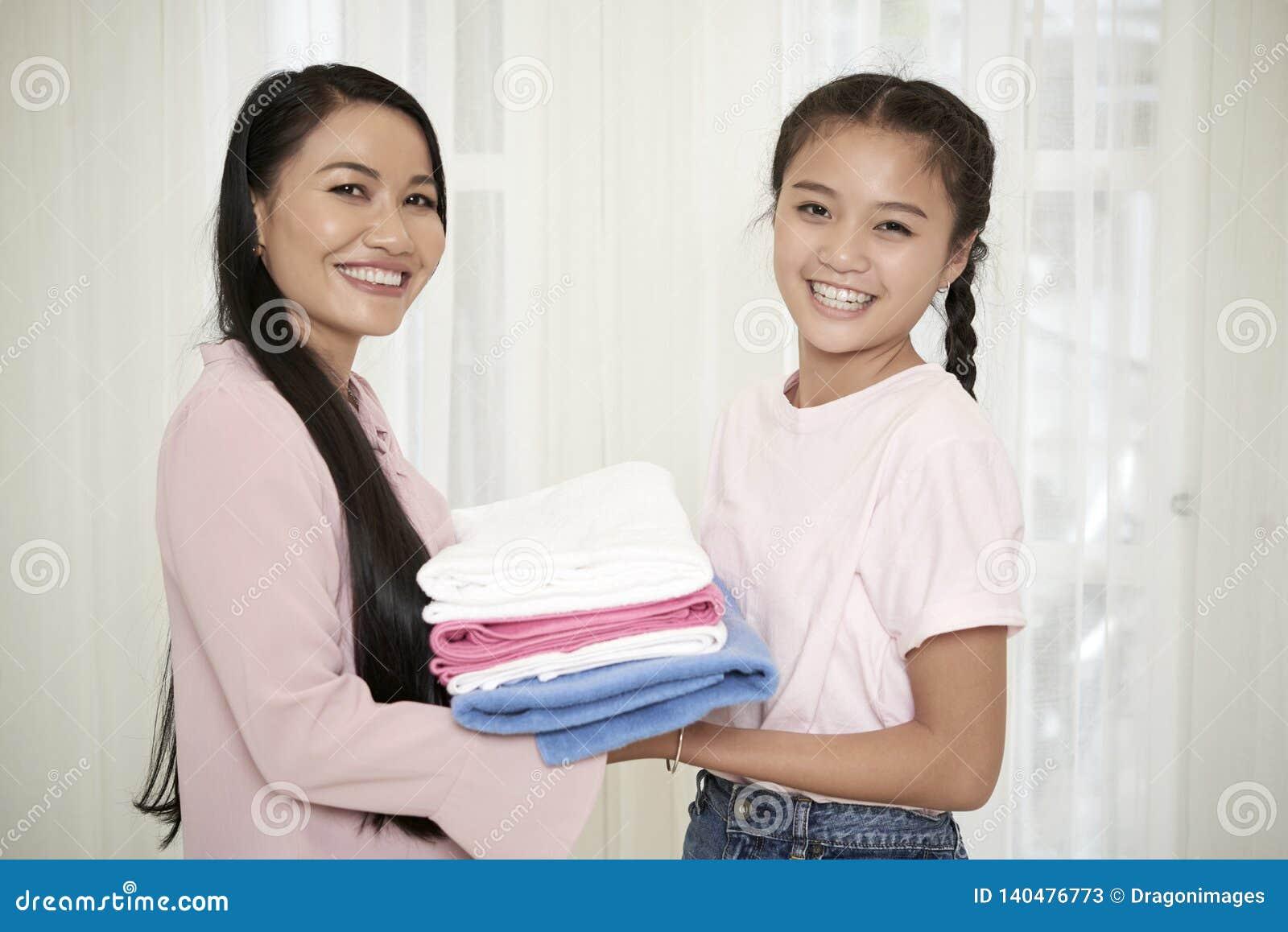 Madre sorridente con la figlia che fa lavoro domestico