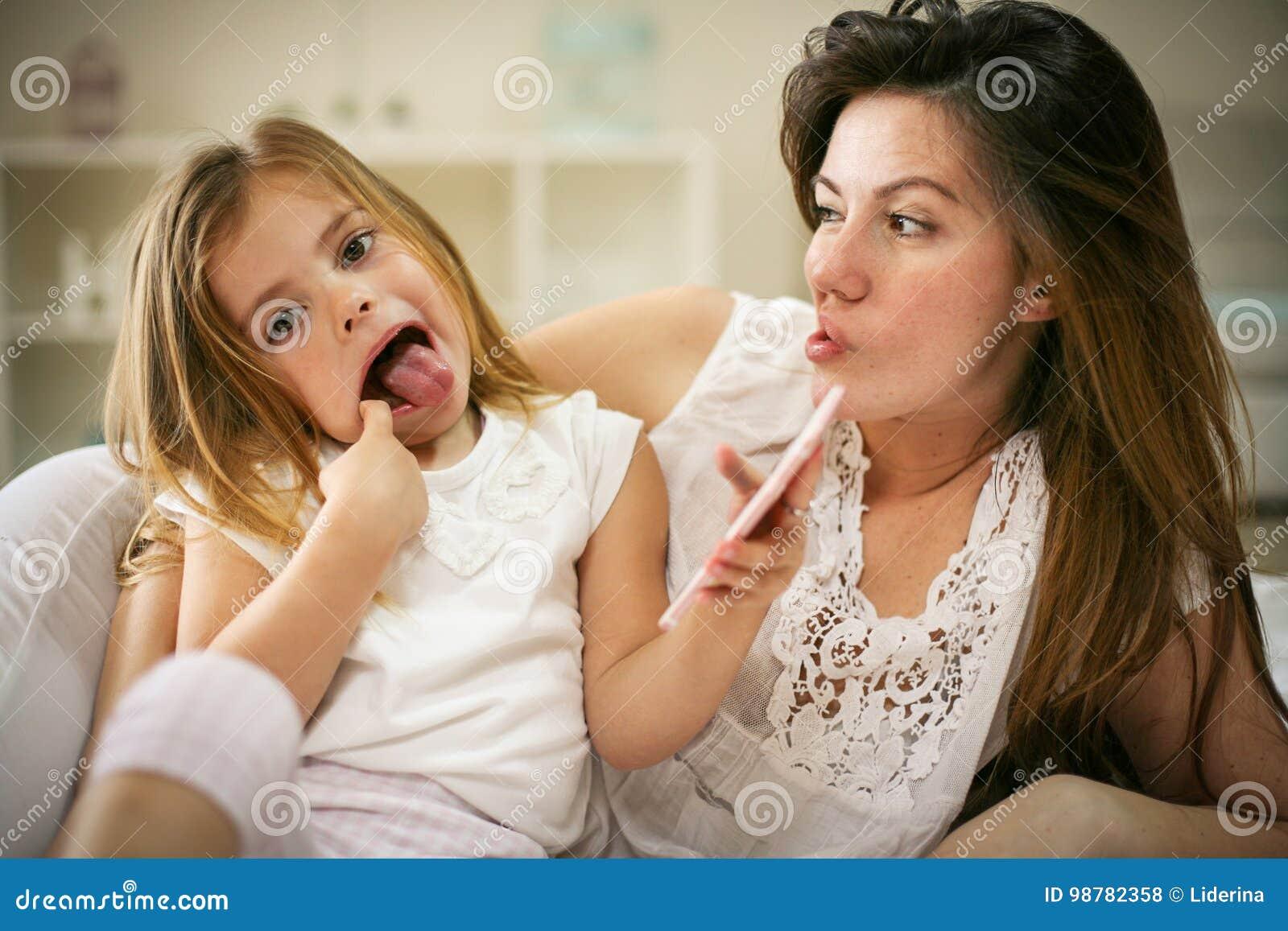 Madre sorridente con la figlia che per mezzo dello Smart Phone sul letto