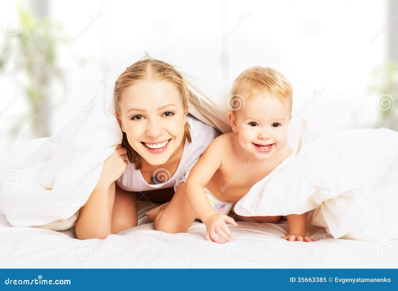 Madre y bebé felices de la familia debajo de las mantas en cama