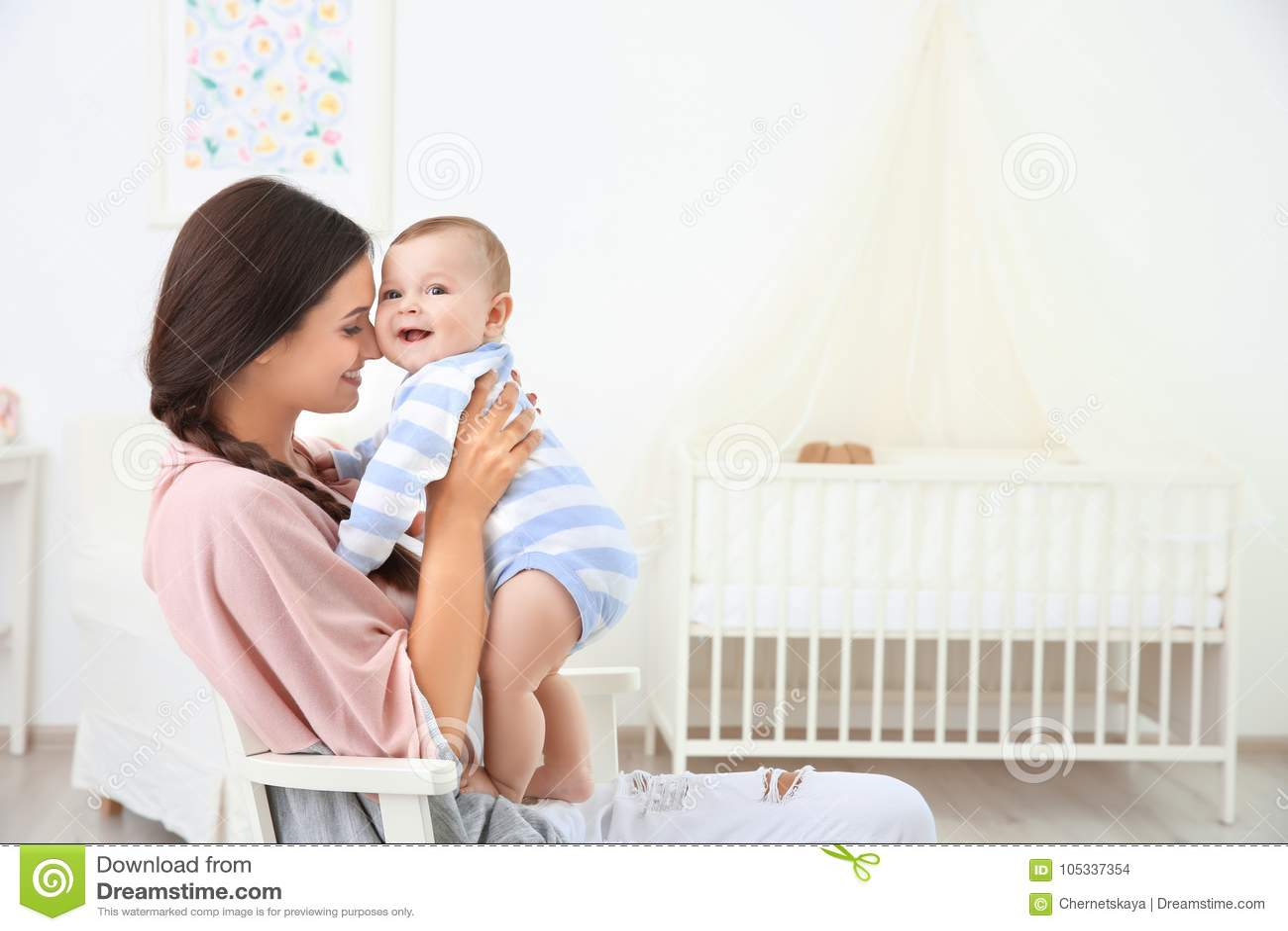 Madre y bebé lindo que se sientan en silla después de bañar