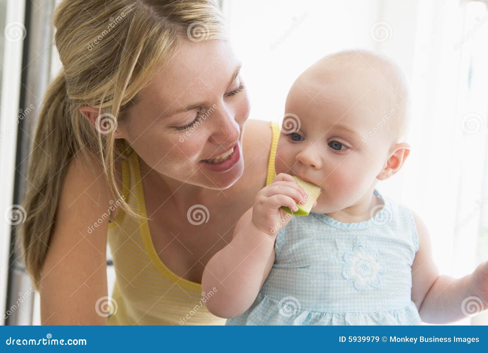 Madre y bebé que comen la manzana