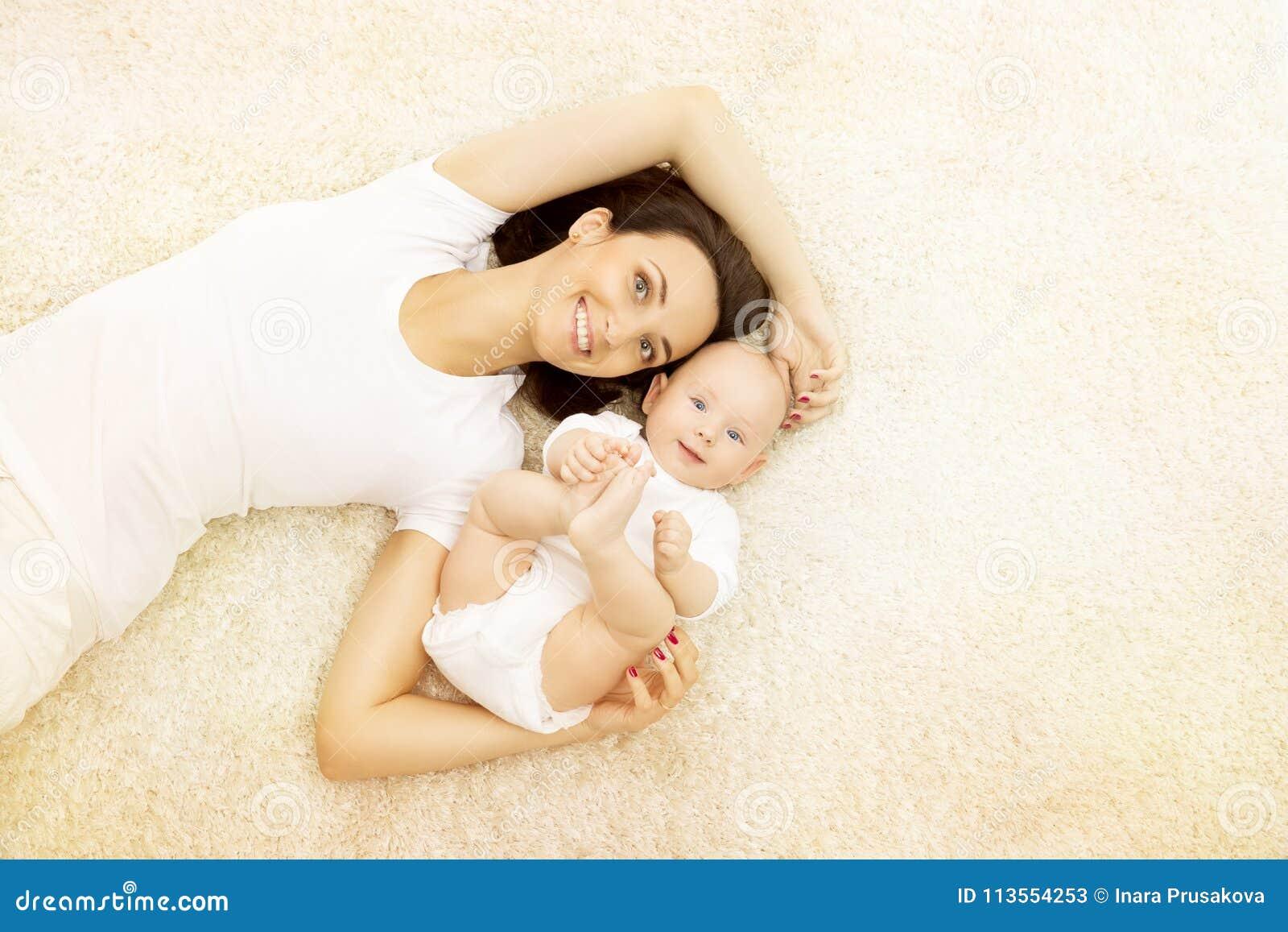 Madre y bebé, retrato feliz de la familia, mamá con el niño en la alfombra