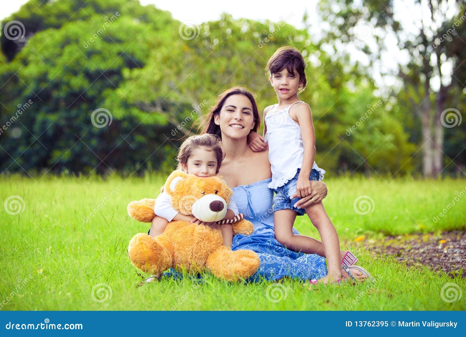 Madre y dos hijas que juegan en hierba