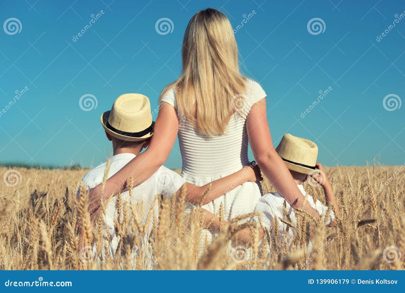 Madre y dos hijos abrazarse y colocarse de mirada de la cosecha del trigo
