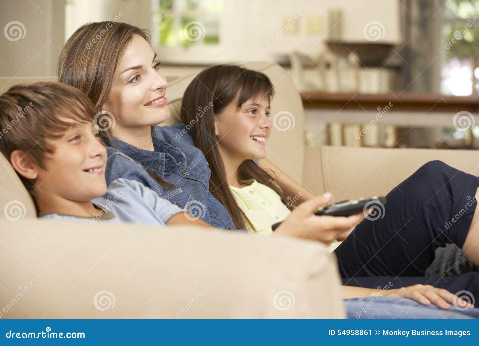 Madre y dos niños que se sientan en Sofa At Home Watching TV junto