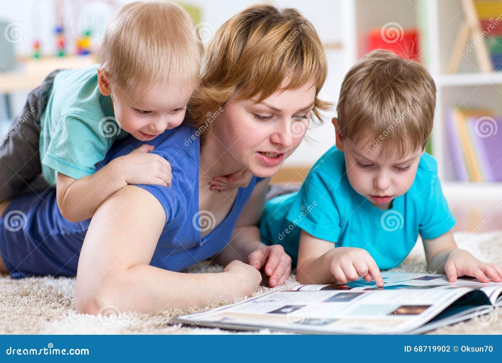 Madre y libro de lectura de los niños en casa