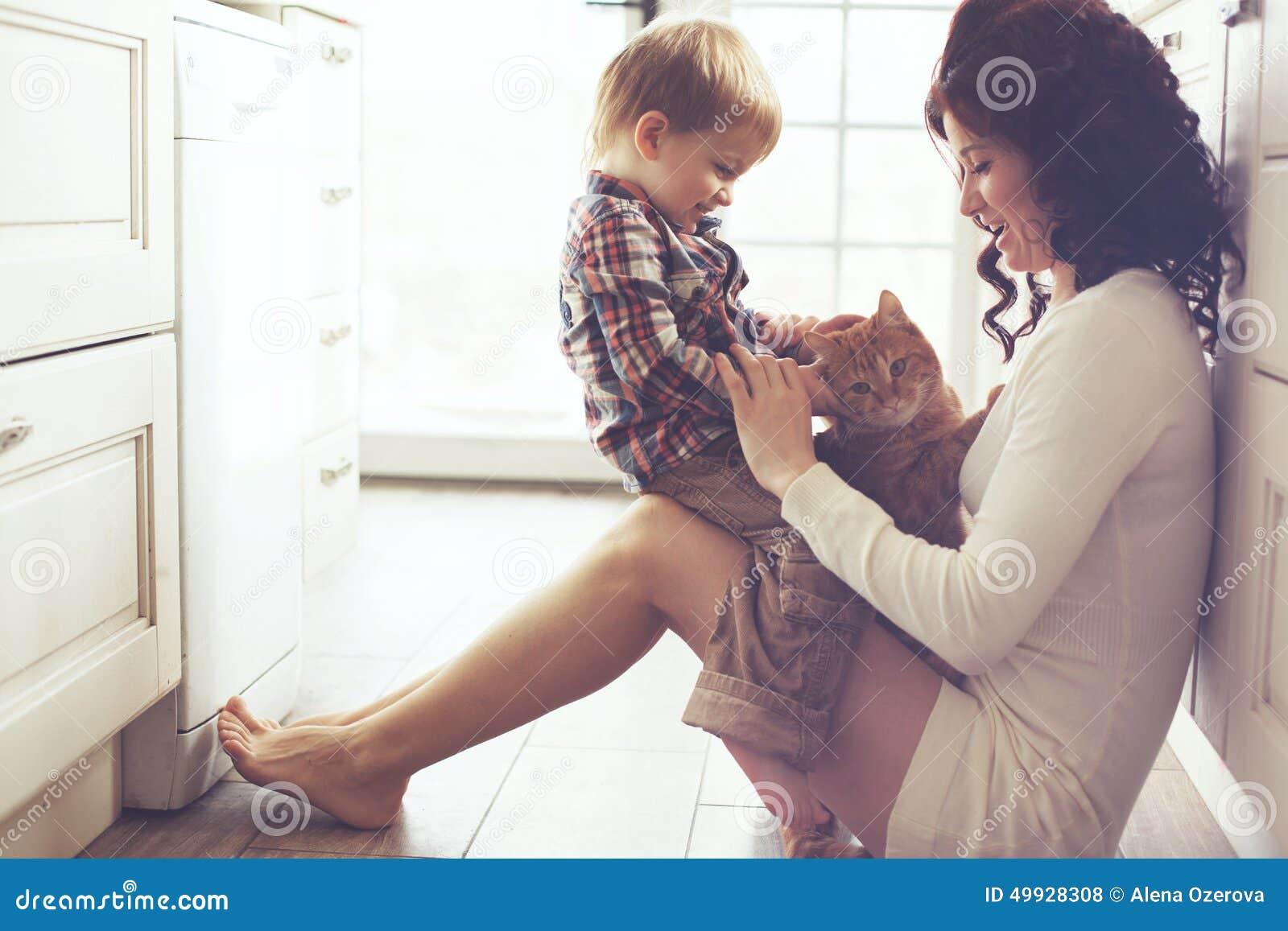 Madre y niño que juegan con el gato
