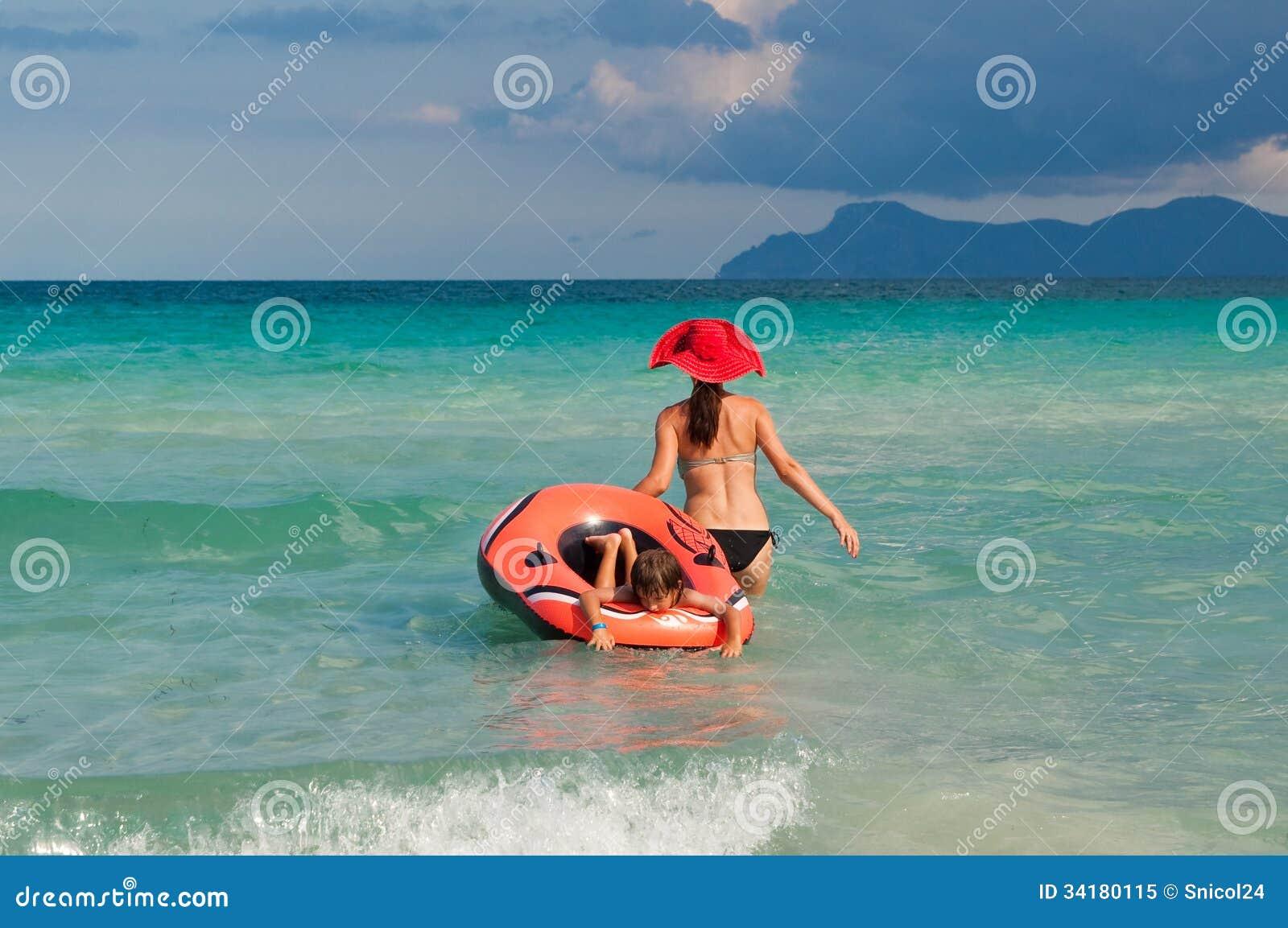 Madre y niño que juegan en ondas