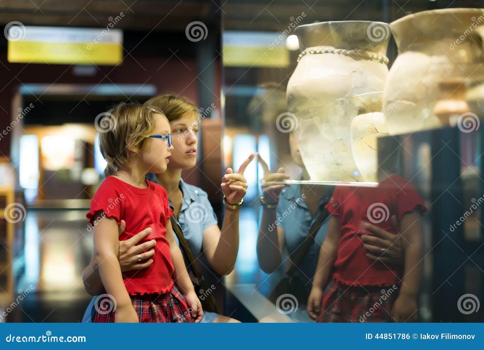 Madre y niño que miran viejos amphores en museo