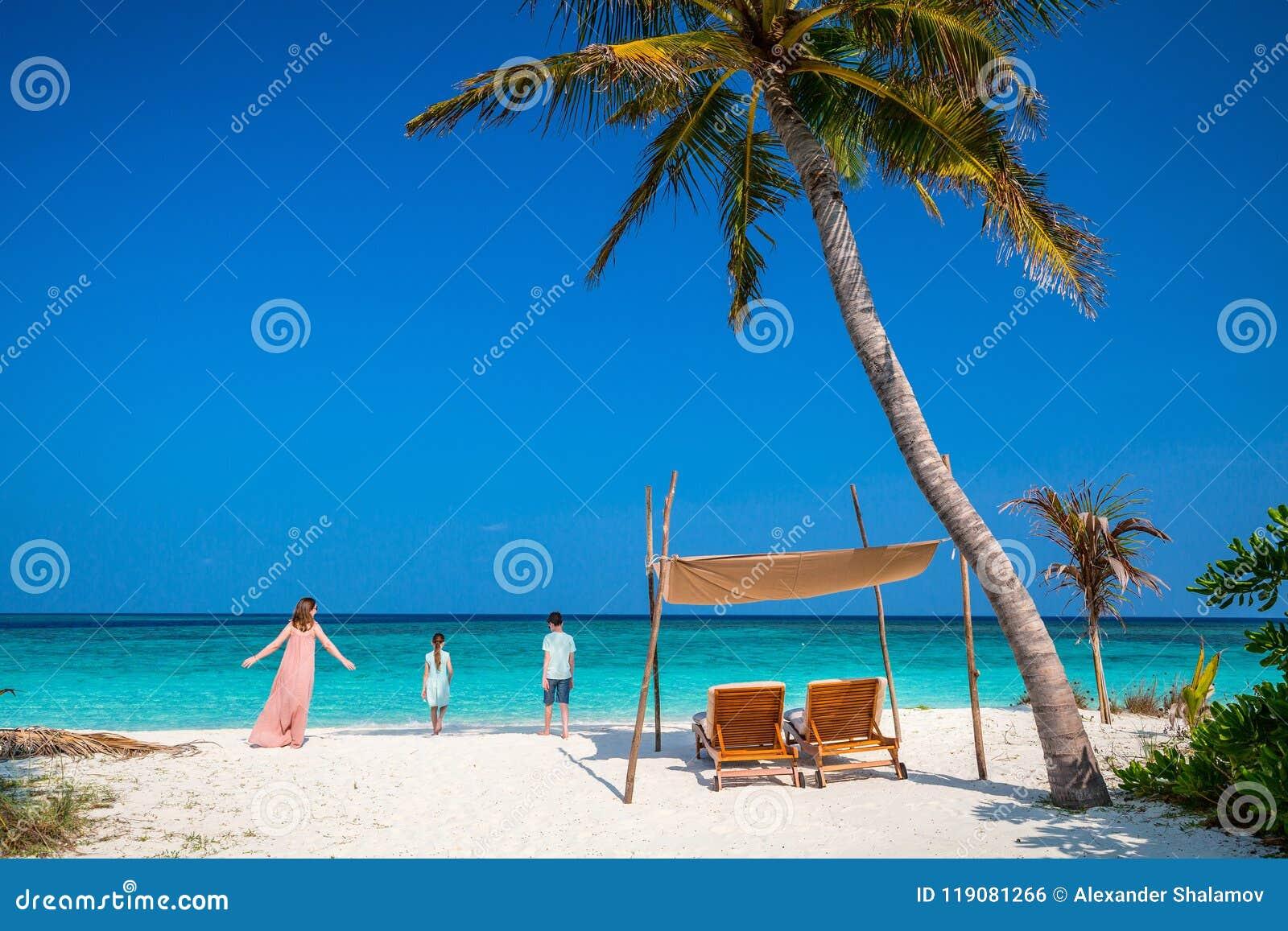 Madre y niños en la playa tropical