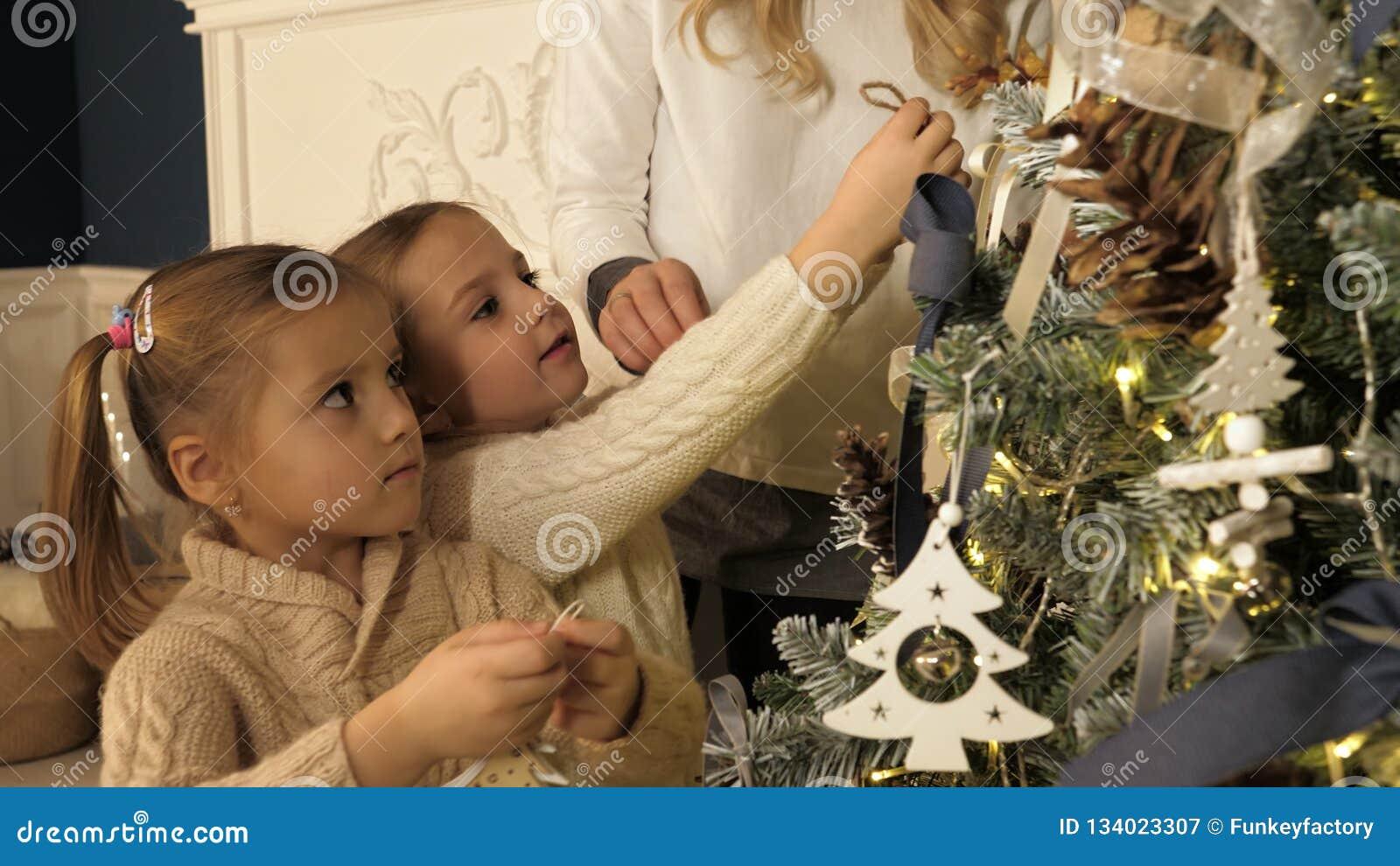 Madre y niños que adornan el árbol de Navidad en sala de estar hermosa de la familia con la chimenea