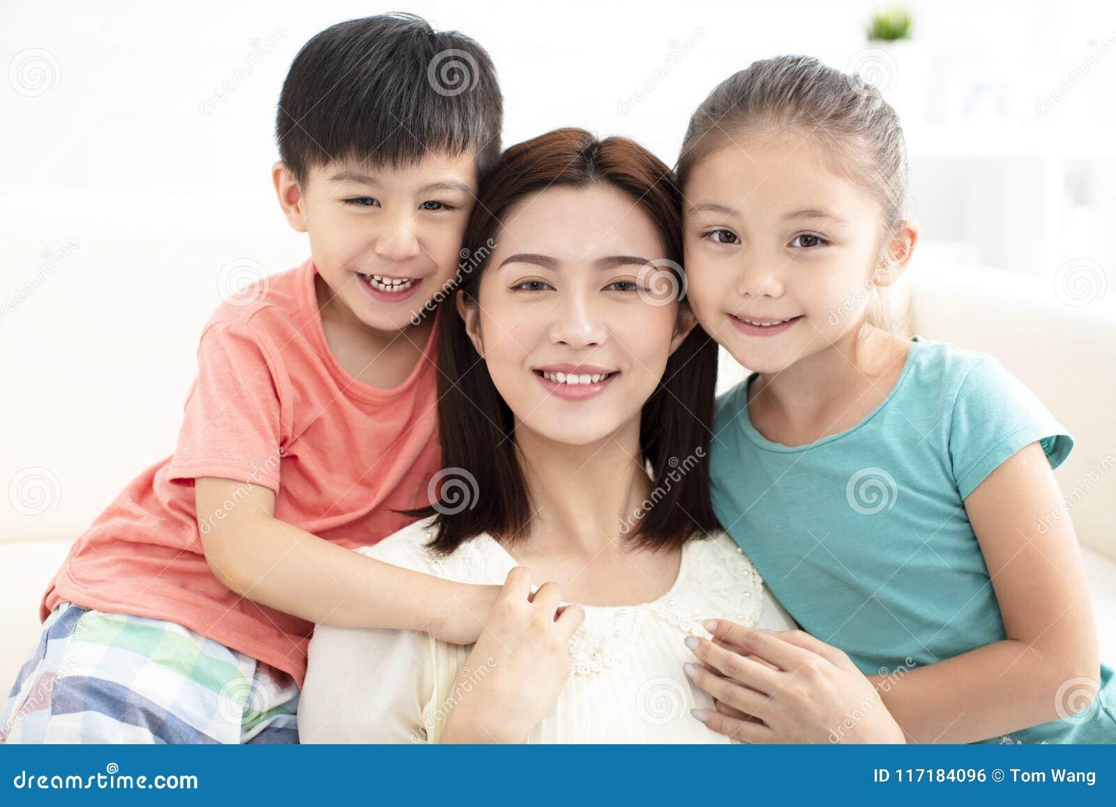 Madre y niños que sonríen en el sofá