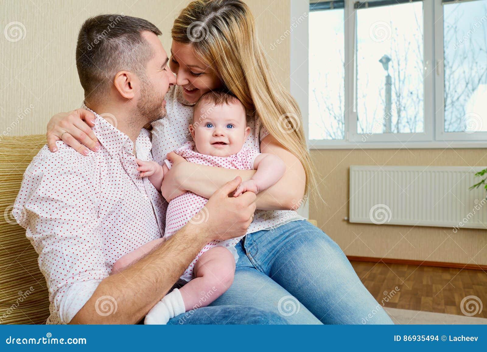 Madre y padre con un bebé en el cuarto que abraza la sonrisa feliz