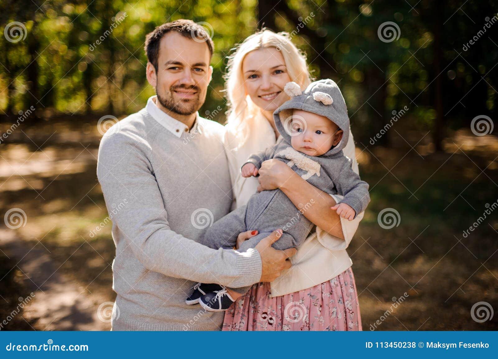 Madre y padre jovenes felices con un hijo lindo del bebé